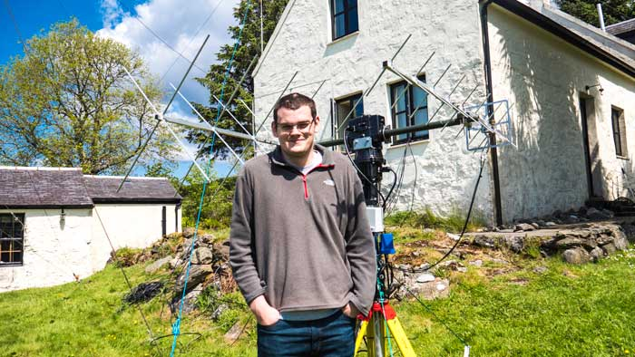 Photograph of Peter 2M0SQL on the Isle of Arran standing in front of some antennas.